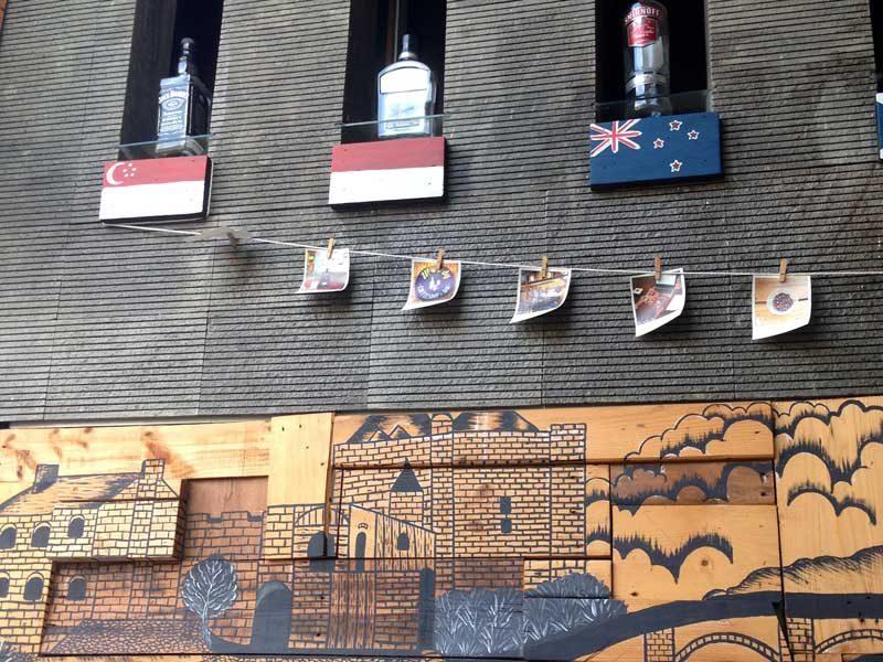 Dekorasi kafe dengan mural dan pajangan foto, bendera dan botol minuman