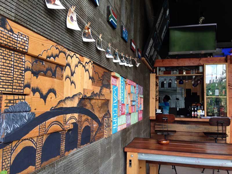 Lukisan dinding dan tumpukan balok kayu berisikan ucapan selamat datang